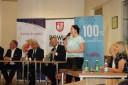 Prezentacja projektów Wojewódzkiego Urzędu Pracy w Krakowie przez Małgorzatę Dudziak na tle banerów powiatu brzeskiego i Gminy Brzesko.