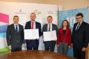 Pięcioro uczestników spotkania stoi za stołem po podpisaniu umowy.