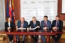 Kobieta i czterech mężczyzn się siedzą przy stole.Dwóch z nich podpisuje porozumienie.