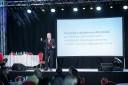 Prowadzący dyskusję z udziałem publiczności redaktor Zbigniew Bartuś stoi na scenie przed mikrofonem.